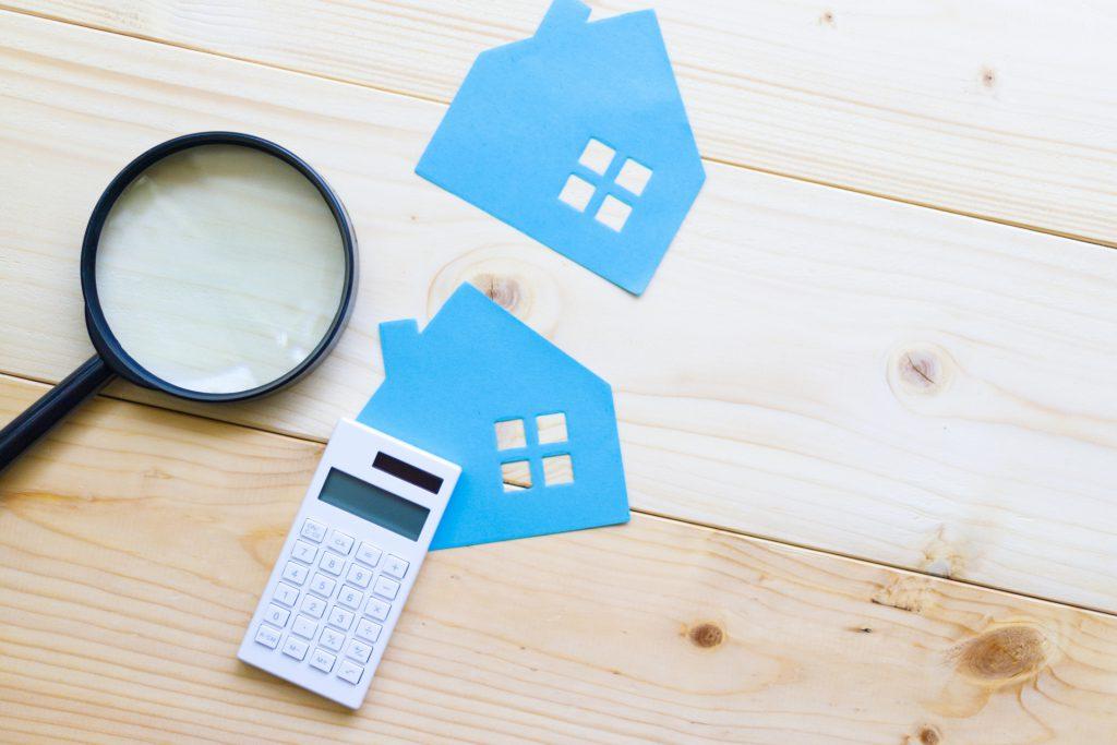 2枚の住宅の切り絵と虫眼鏡と電卓