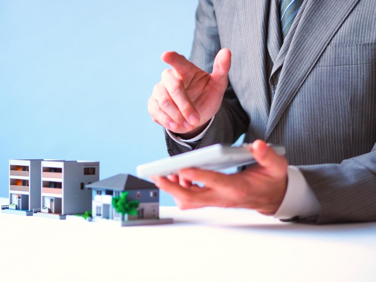 住宅の模型を前に電卓を叩くスーツ姿の男性
