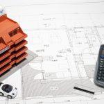 住宅の設計図とマンションの模型と電卓