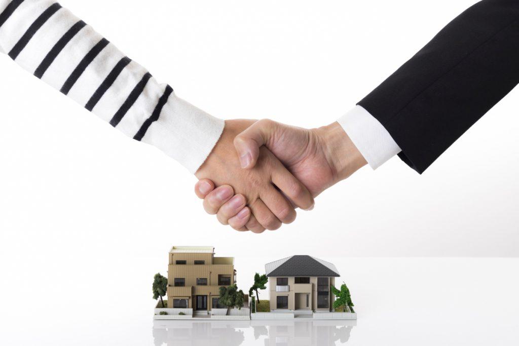 住宅の模型を前に握手を交わす手