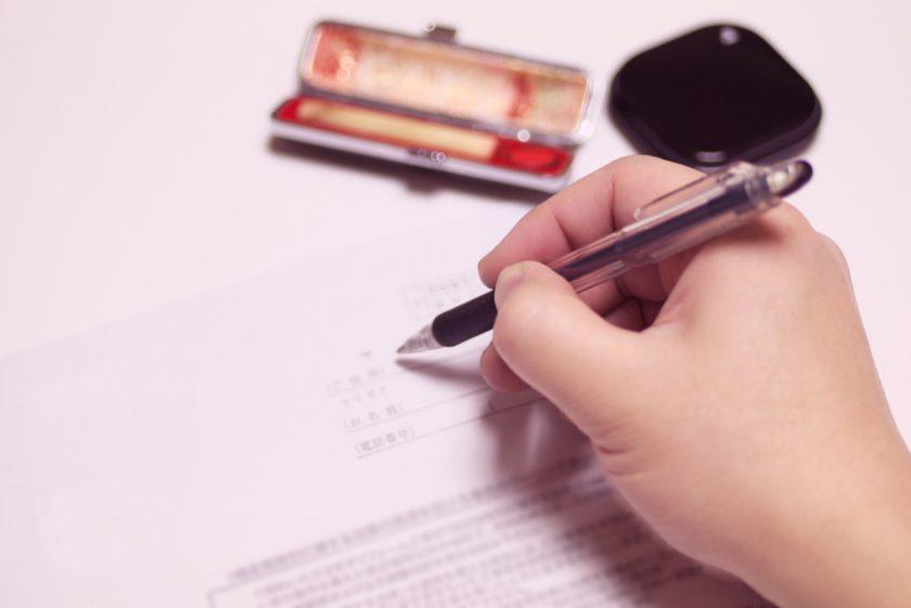 書類に署名をする手と印鑑