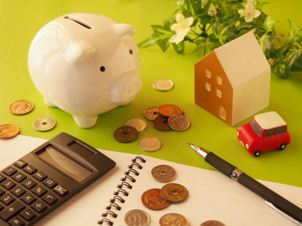 豚の貯金箱と小銭と電卓と住宅の模型