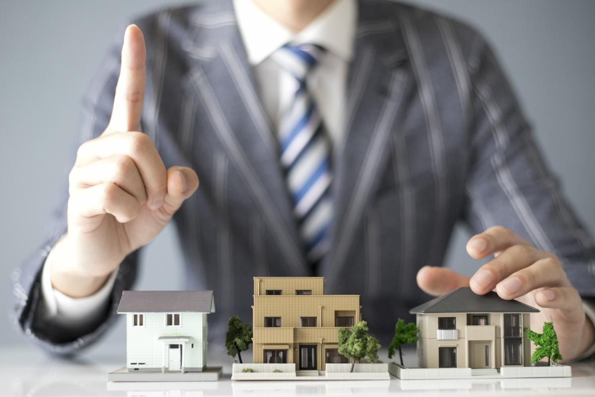 住宅の模型を前に人差し指を立てるスーツの男性