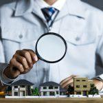 住宅の模型を虫眼鏡でチェックする作業服の男性