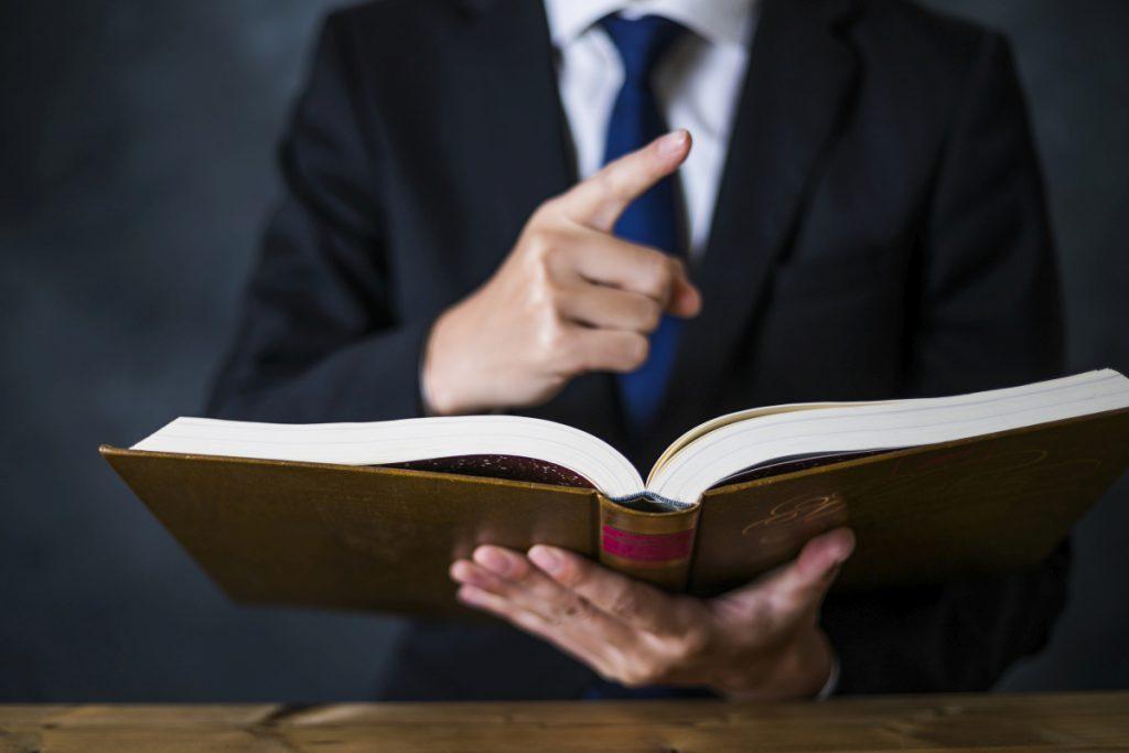 厚い本を手に人差し指を立てて解説をするスーツの男性