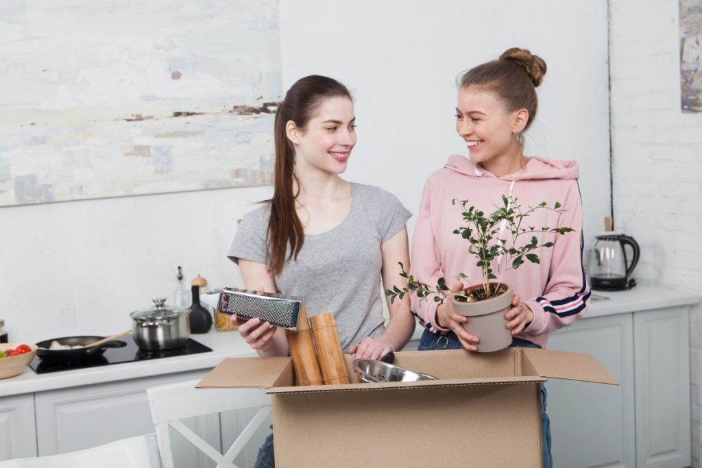 キッチンで段ボール箱に荷物を詰める女性2人