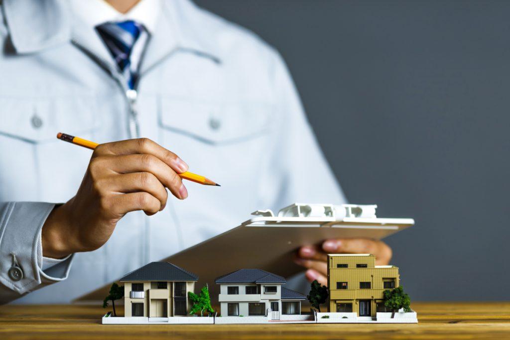 住宅の模型をクリップボード片手にチェックする作業服の男性