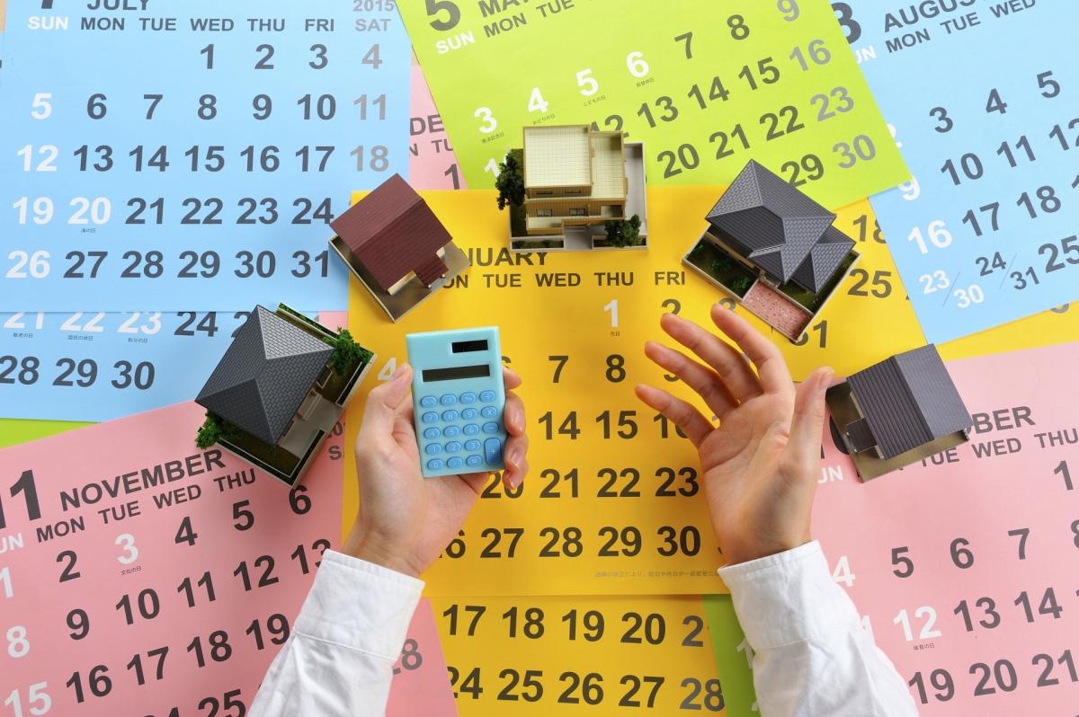 カレンダーを下敷きに並べられた住宅の模型と電卓