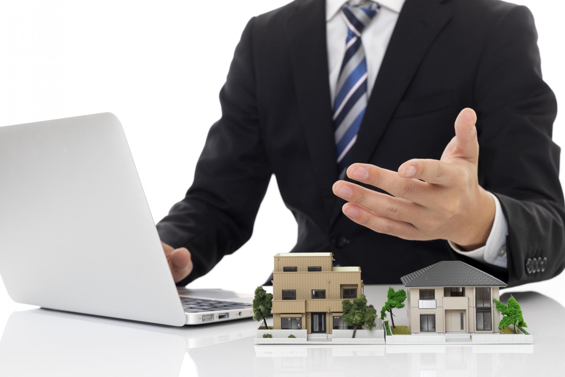 住宅の模型を前にパソコンを使いながら説明をするスーツの男性
