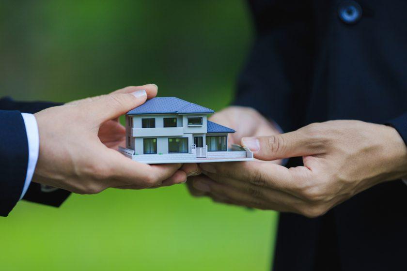 住宅の模型を受け渡しする手