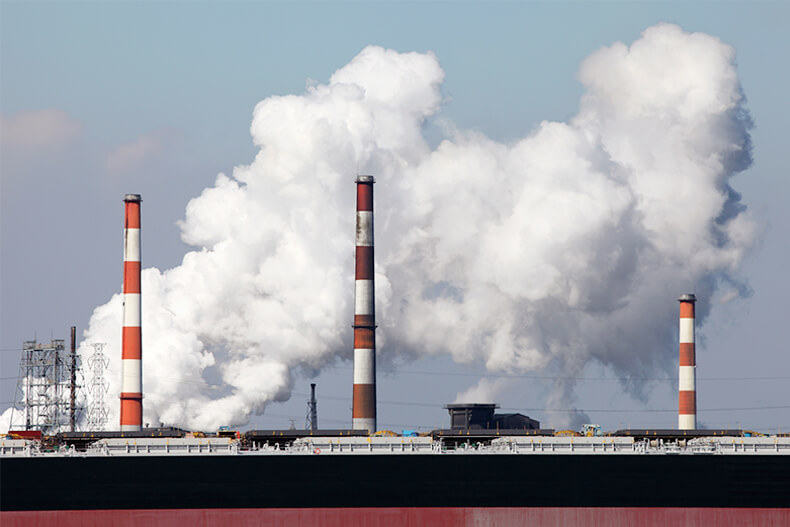 煙が立ち上る工場地帯の煙突