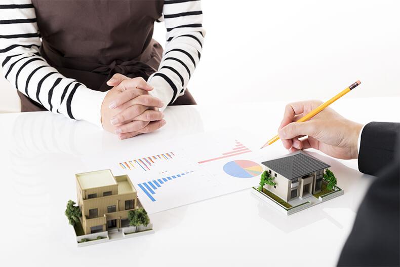 専門業者へ物件の売却について相談する女性と家の模型
