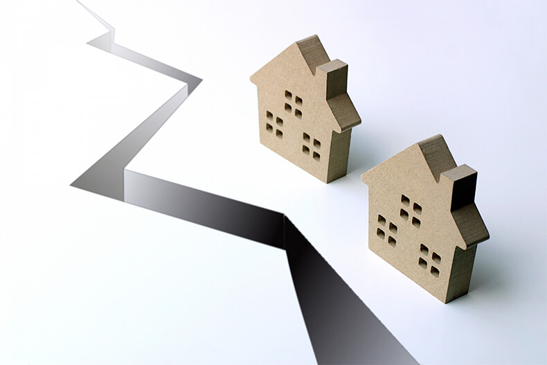 家の模型とひび割れた地面
